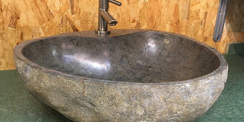évier en pierre de rivière avec un évidement pour placer un robinet sur l'évier